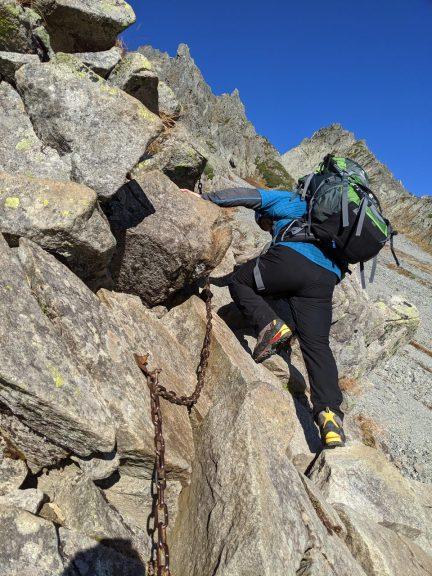ザイテングラート鎖場を重い荷物を背負って登る人