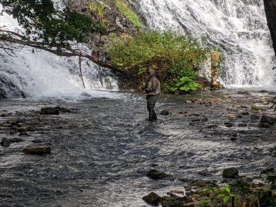湯滝の下で釣りをする人